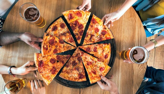 hands reaching for pizza in the middle of a table