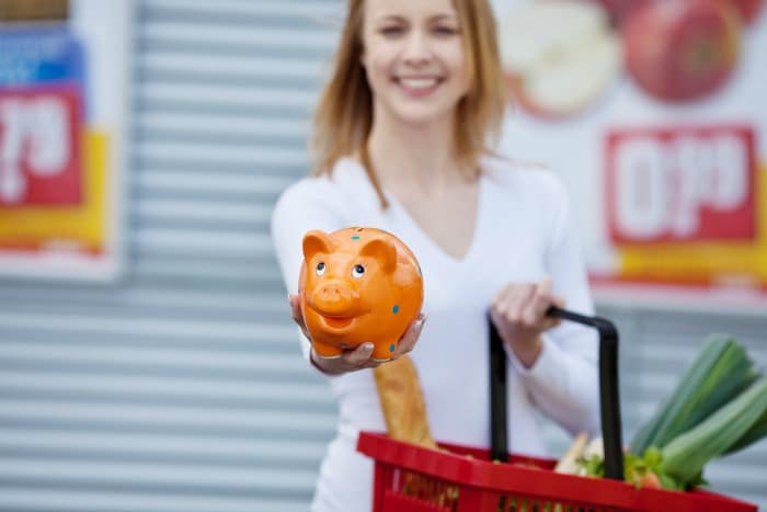 happy young woman showing piggybank while holding shopping basket