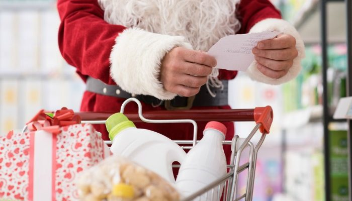 Santa Claus doing grocery shopping at the supermarket, he is pushing a full cart and checking a list