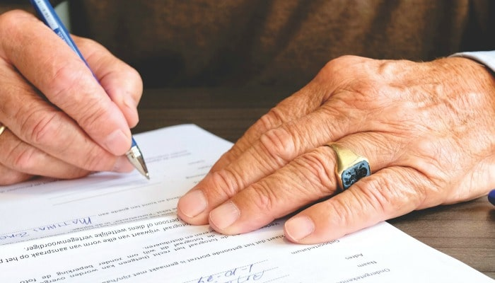 old man signing contract