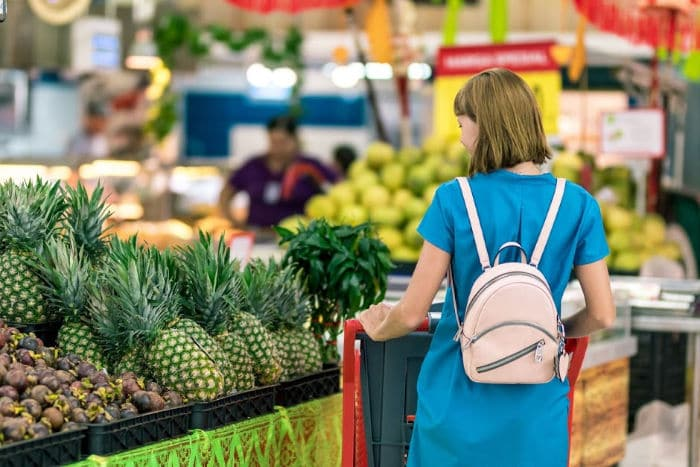 woman shopping in fruit and veg aisle