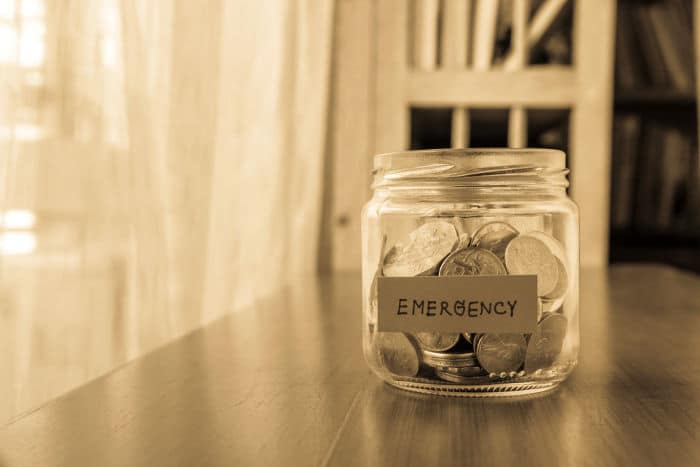 A savings money jar with world coins and emergency word on label