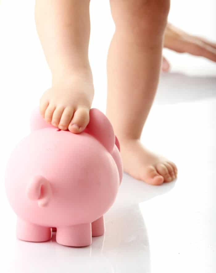 Baby legs on piggy bank - isolated
