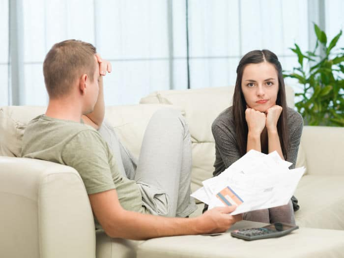 worried couple doing their accounts at home