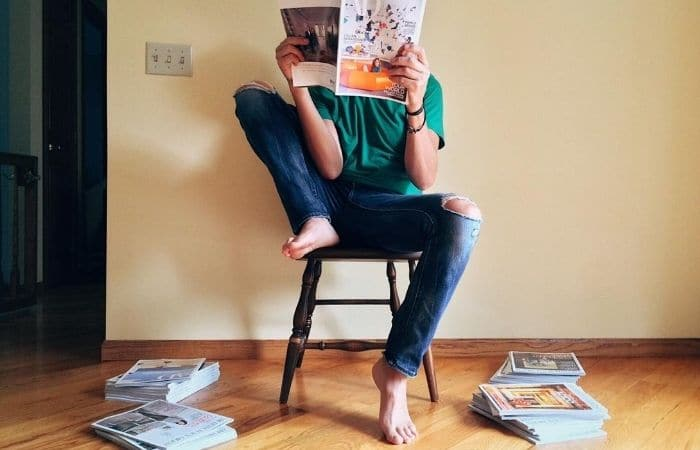 man reading magazines on a chair