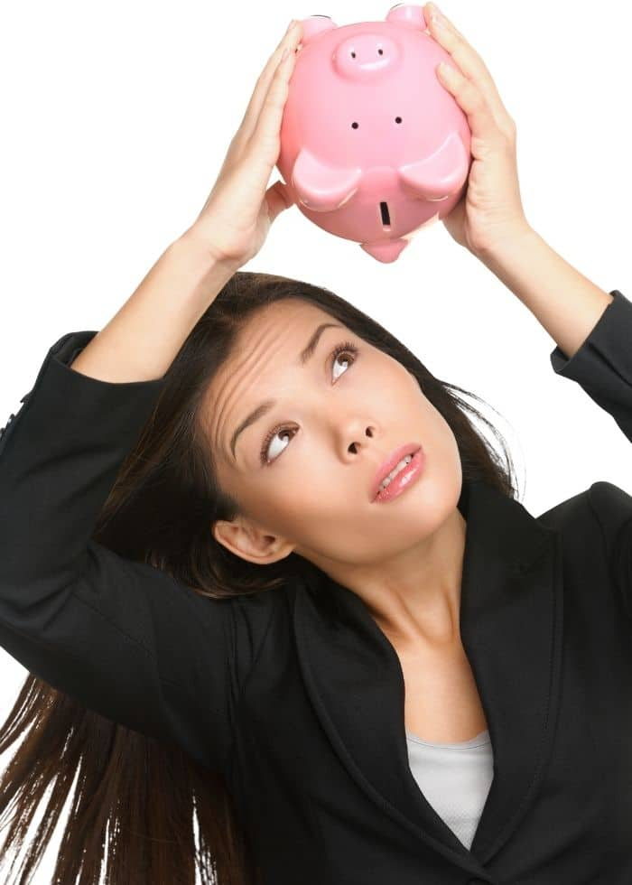 woman looking for money in piggy bank