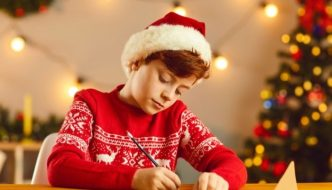 boy wearing a Christmas jumper writing a letter