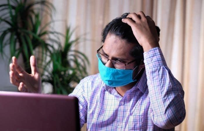 Man wearing mask using laptop