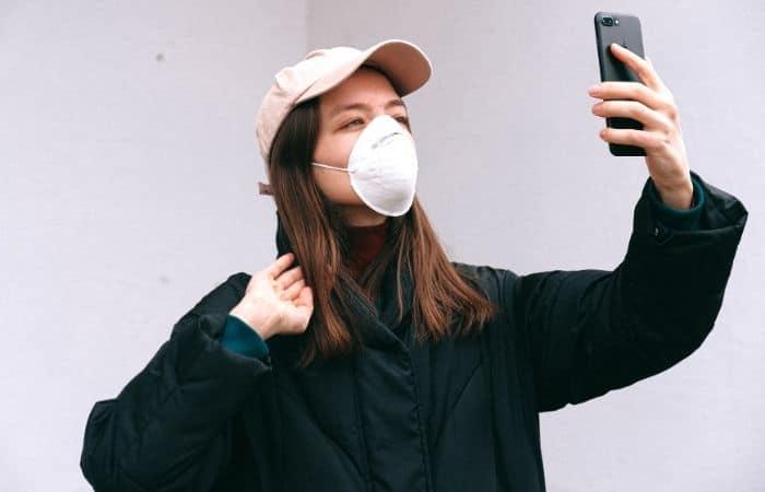 Woman wearing mask holding phone