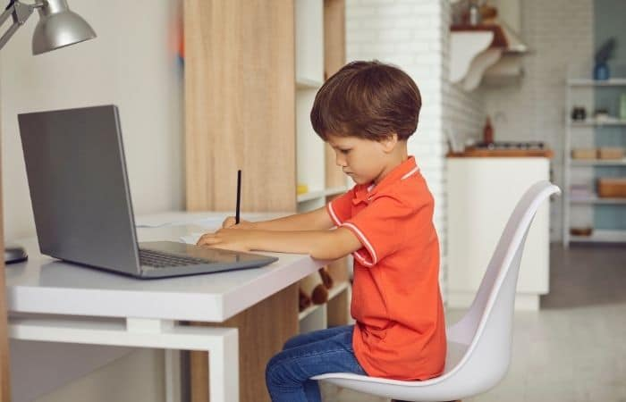 child writing next to laptop
