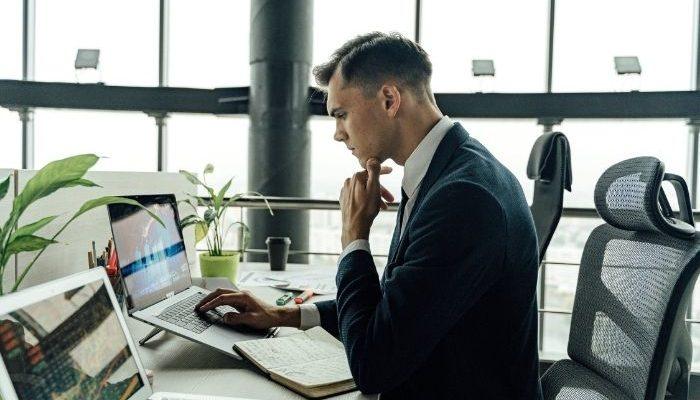 man in black suit jacket using macbook pro