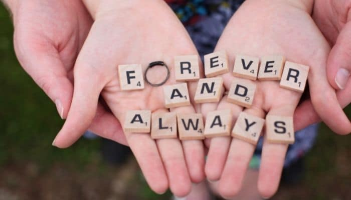 always and forever scrabble tiles held by couples hands