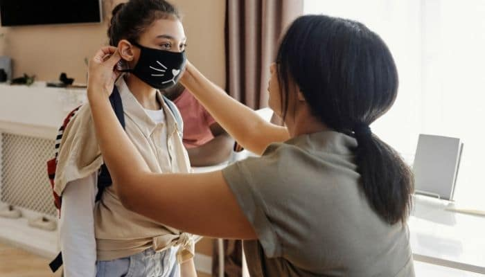 parent helping child with mask