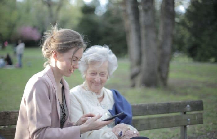 young and old woman looking at phone