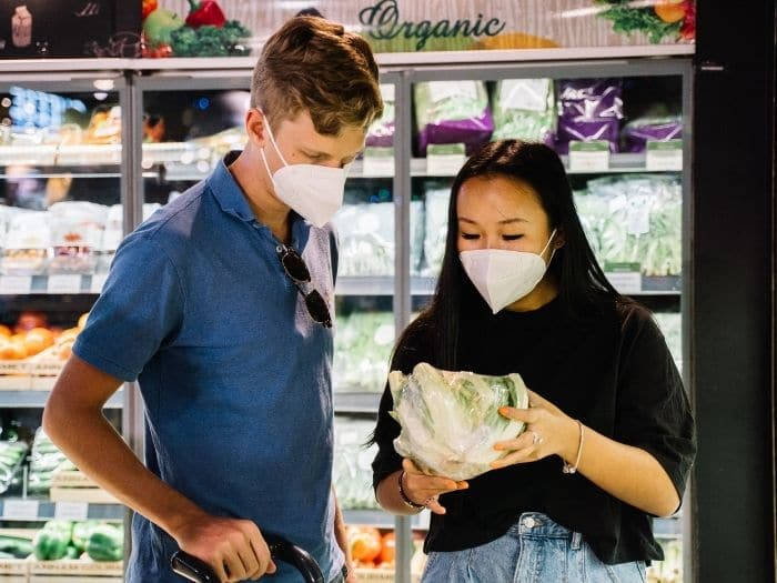 couple wearing face masks in supermarket