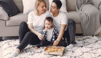 family eating a pizza while sat on a rug in front of a sofa
