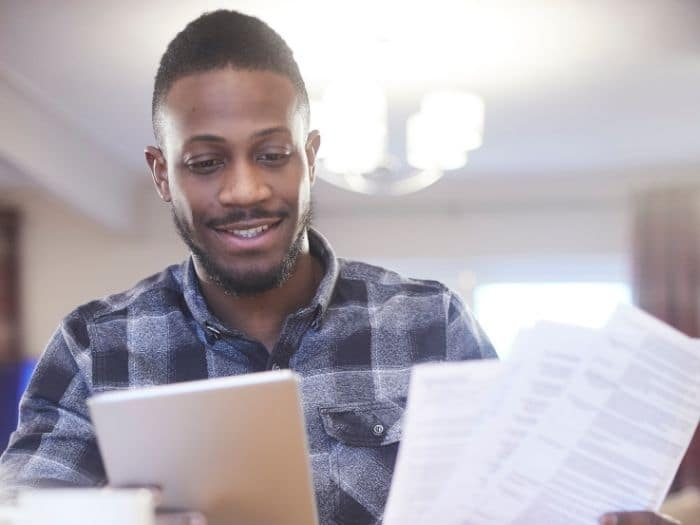 Man smiling while looking at energy bills