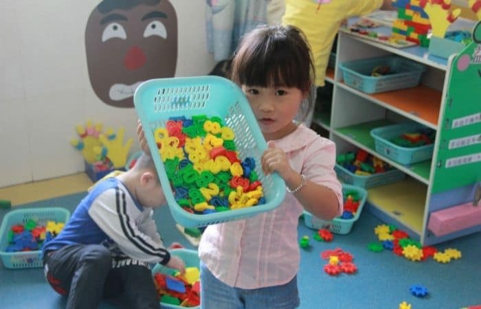 young girl holding basket of number magnets