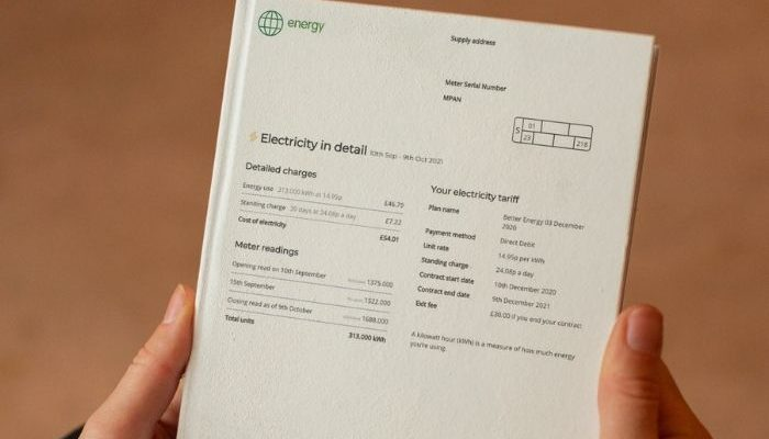 person holding an electric bill