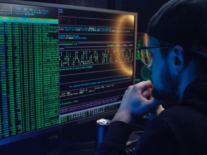 man staring at a screen with computer code