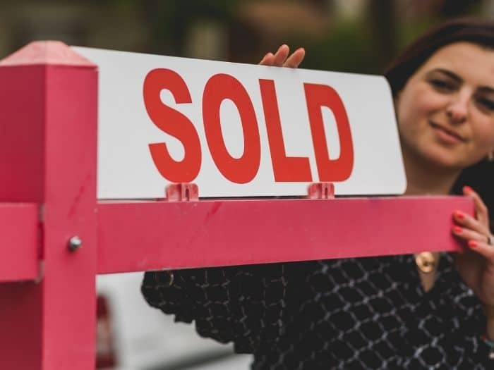 woman holding a house sold sign