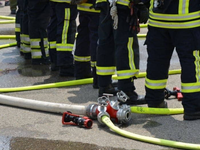 firefighters in suit standing over hose