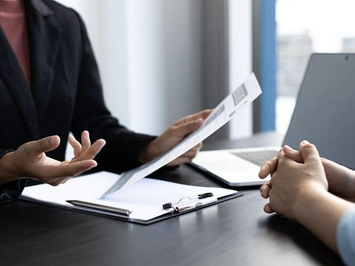 woman holding a CV interviewing another person