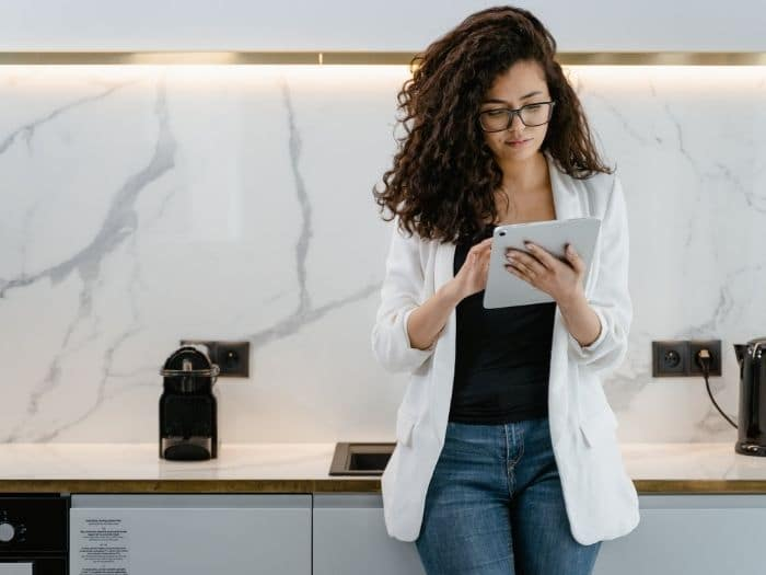 smarty dressed woman in a kitchen looking at an ipad