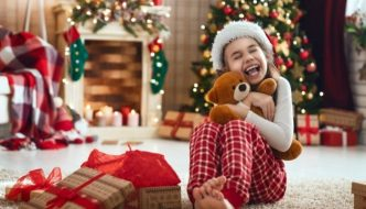 overwhelmed kid sitting in front of presents under the tree