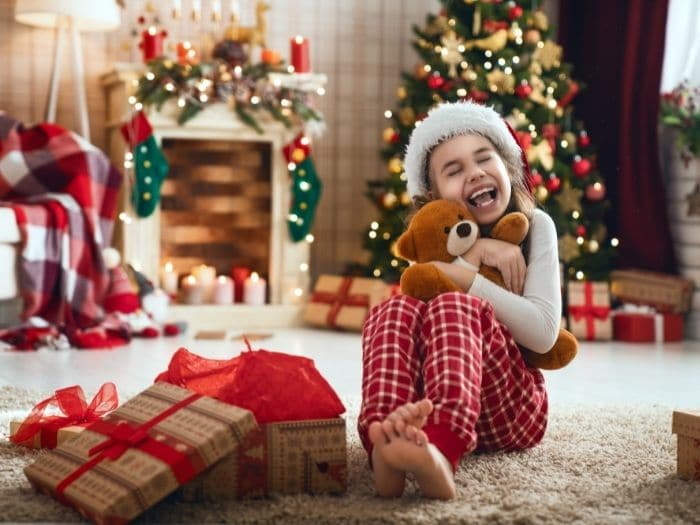 overwhelmed child sits in front of gifts under the tree