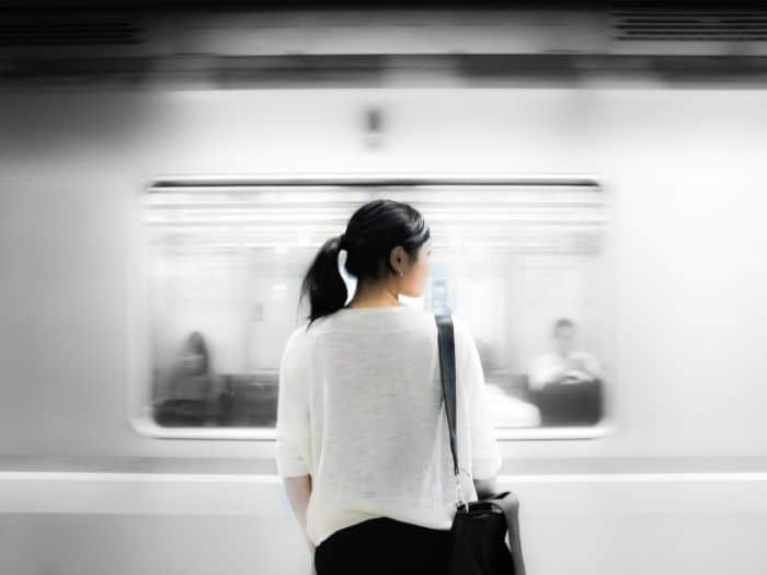 woman looking at a train speeding past