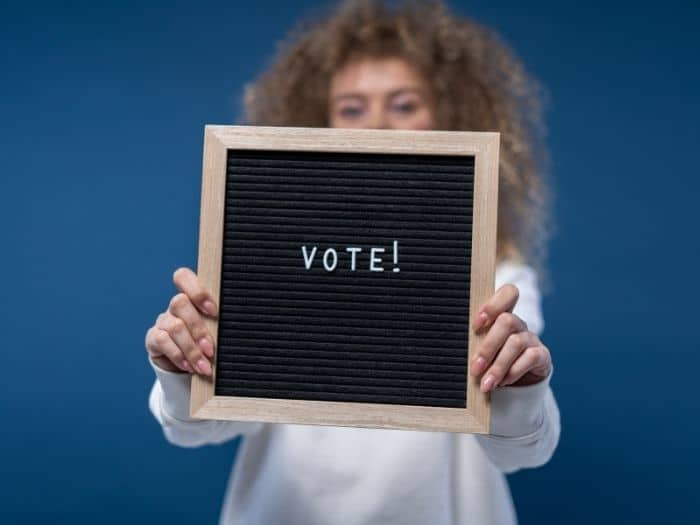 woman holding a board which reads vote